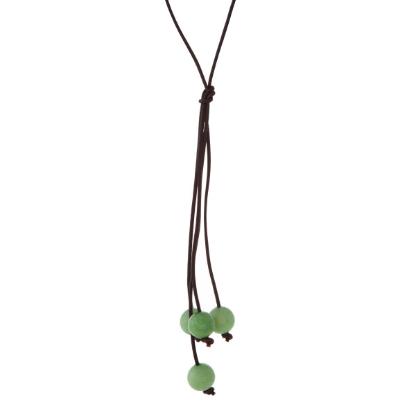 """Brown cord necklace with a green natural stone beaded tassel. Approximately 32"""" in length."""