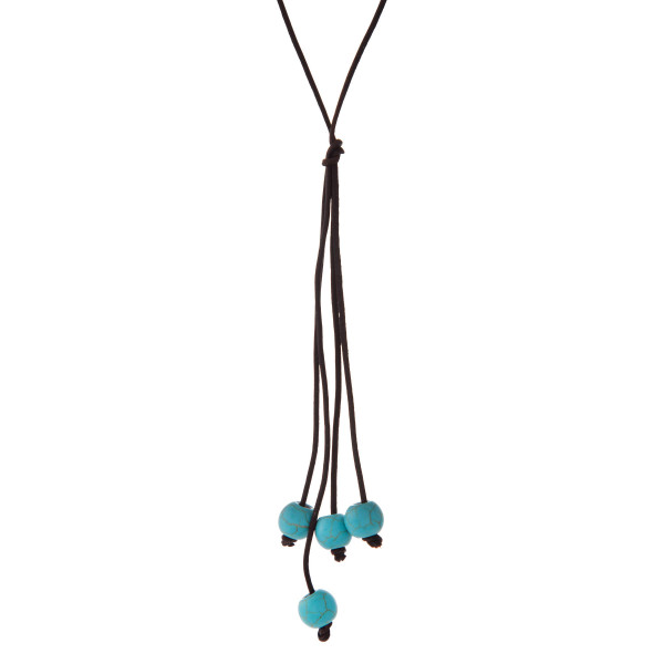 "Brown cord necklace with a turquoise natural stone beaded tassel. Approximately 32"" in length."