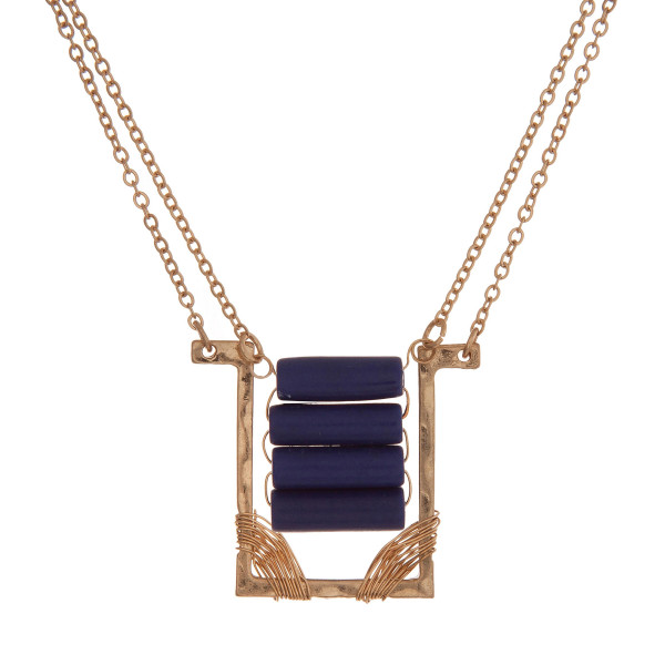 "Dainty gold tone necklace with a rectangle pendant and royal blue beads. Approximately 16"" in length."