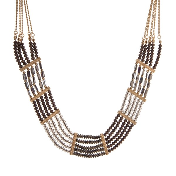 """Gold tone statement necklace with bronze, gray, and Dalmatian beads. Approximately 18"""" in length."""