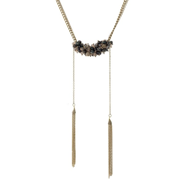 """Burnished gold tone necklace with gray and beige beads and two chain tassels. Necklace is approximately 20"""" in length and tassels are approximately 5"""" in length."""