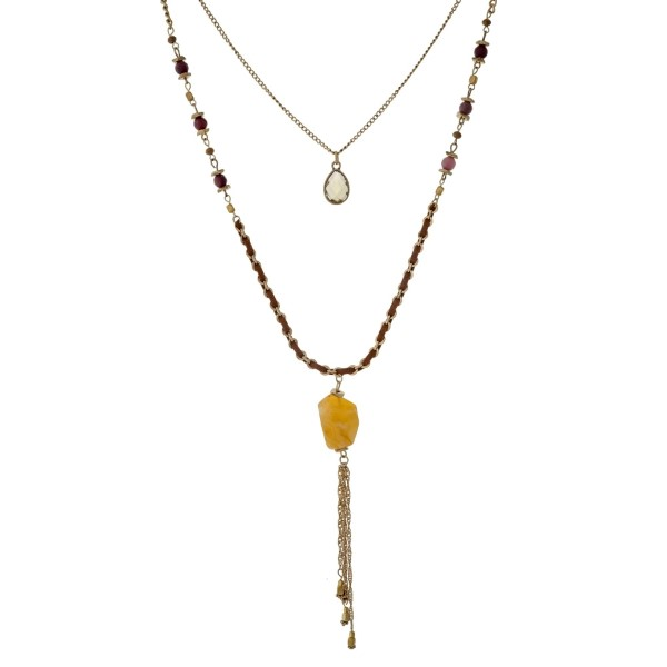 """Burnished gold tone double layer necklace with navy bronze beads, brown thread, a tan crystal pendant, and a chain tassel. Approximately 32"""" in length."""