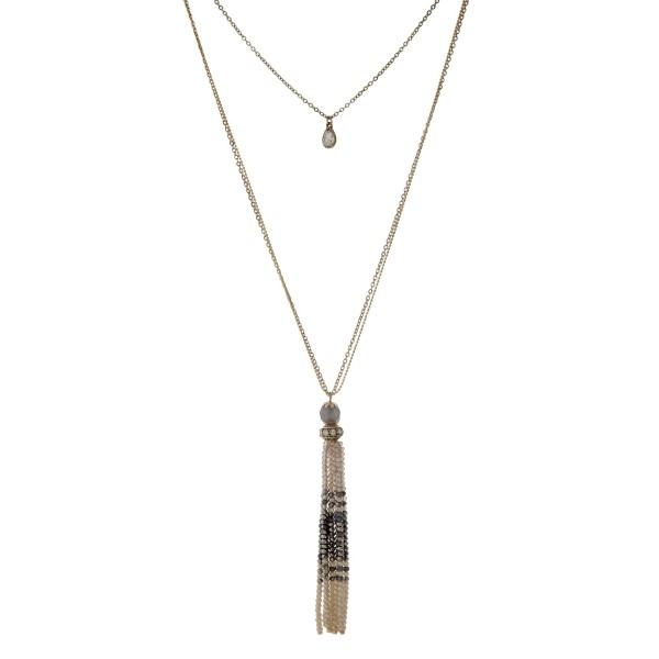 """Gold tone necklace with a gray to ivory ombre beaded tassel. Approximately 32"""" in length."""