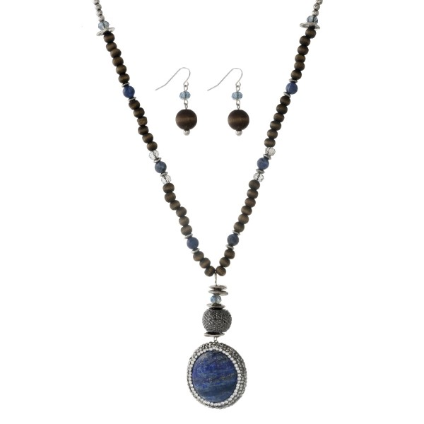 "Silver tone beaded necklace with brown wooden beads and a pave blue pendant. Approximately 32"" in length."