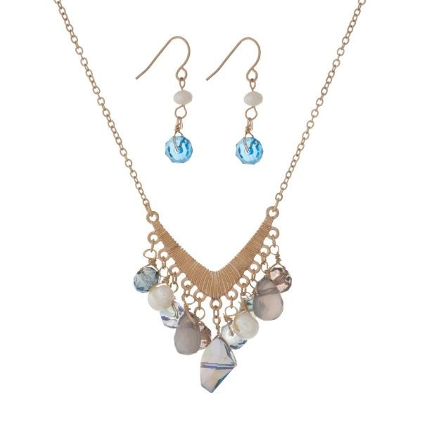 "Gold tone necklace set with a 'v' shaped pendant and blue bead charms. Approximately 18"" in length."