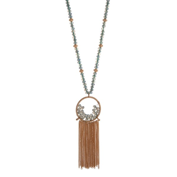 "Gold tone necklace displaying blue iridescent beads and a wire wrapped fringe pendant. Approximately 32"" in length."