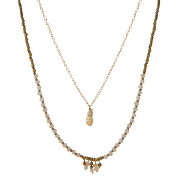 "Gold tone double layer necklace with brown and ivory beads and a beige teardrop pendant. Approximately 24"" in length."