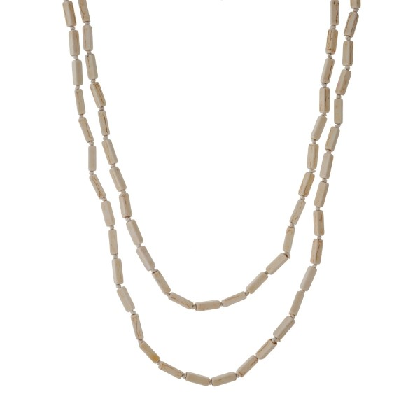 "Knotted, ivory wrap necklace with rectangle stones. Approximately 60"" in length."