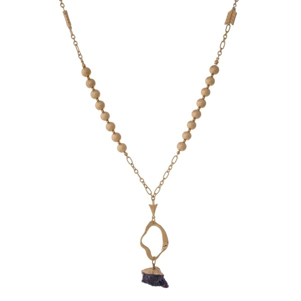 """Gold tone necklace with a hammered open pendant and a purple natural stone. Approximately 32"""" in length."""