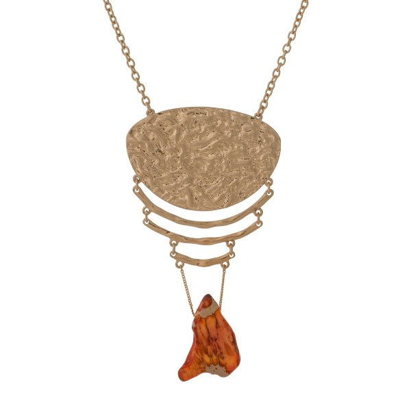 """Gold tone necklace with a hammered pendant and an orange natural stone. Approximately 32"""" in length."""