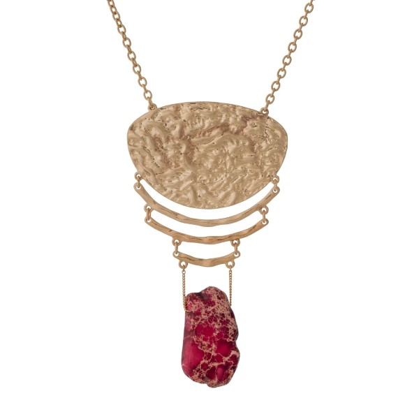 """Gold tone necklace with a hammered pendant and a red natural stone. Approximately 32"""" in length."""