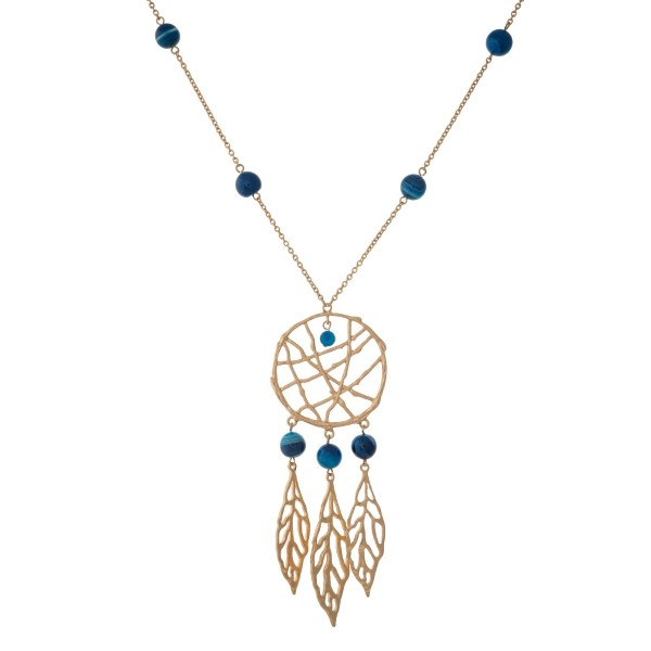 """Gold tone necklace with navy blue beads and a dream catcher pendant. Approximately 32"""" in length."""