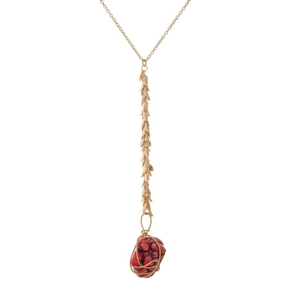 """Gold tone 'Y' necklace with fringe and a wire wrapped red nugget stone. Approximately 32"""" in length."""