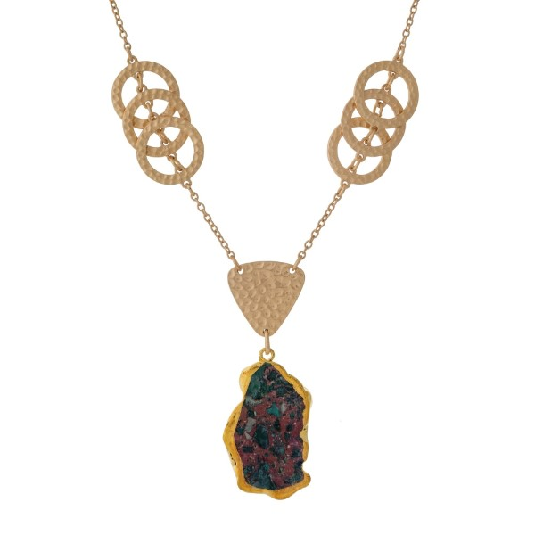 """Gold tone necklace with hammered rings and a green agate stone. Approximately 32"""" in length."""