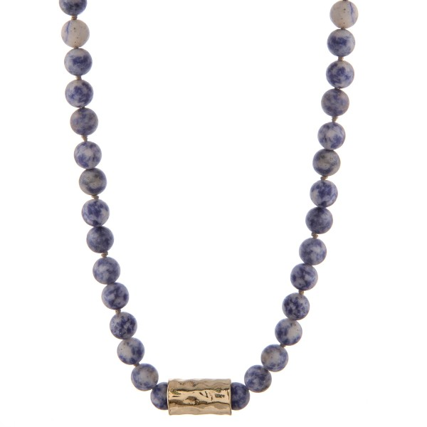 "Matte sodalite beaded necklace with a hammered gold tone cylinder. Approximately 18"" in length."