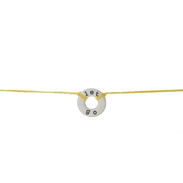 """Yellow cord necklace with a silver tone disc, stamped with """"let go."""" Approximately 16"""" in length."""