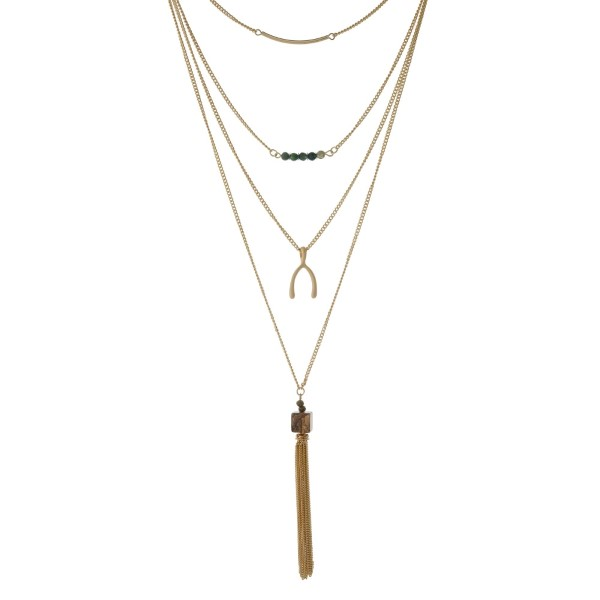 """Gold tone multi layer necklace with green beads, a wish bone, and a chain tassel. Approximately 24"""" in length."""