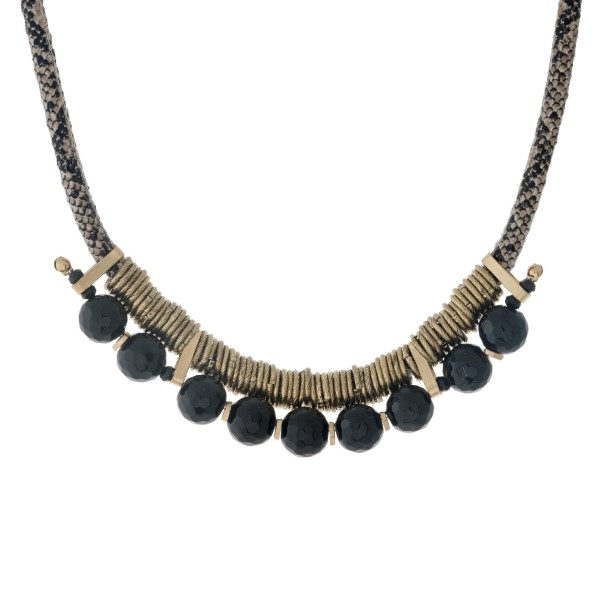 """Snake skin necklace with gold tone wire wrapped black faceted beads. Approximately 14"""" in length."""