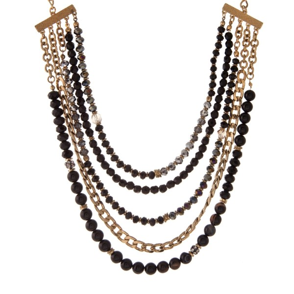"""Gold tone necklace with five layers of black and gray faceted beads. Approximately 16"""" in length."""