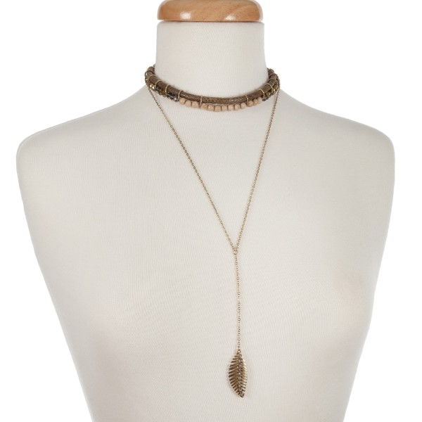 "Gold tone double layer necklace with a snake skin pattern and ivory beaded choker and a 'Y' layer displaying a leaf pendant. Approximately 12"" in length."