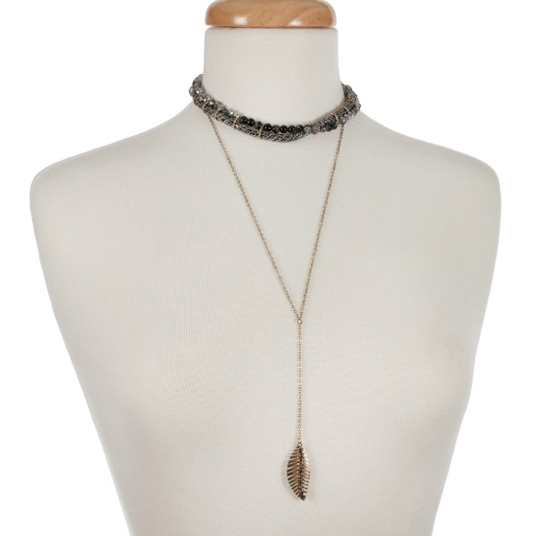 "Gold tone double layer necklace with a snake skin pattern and gray beaded choker and a 'Y' layer displaying a leaf pendant. Approximately 12"" in length."