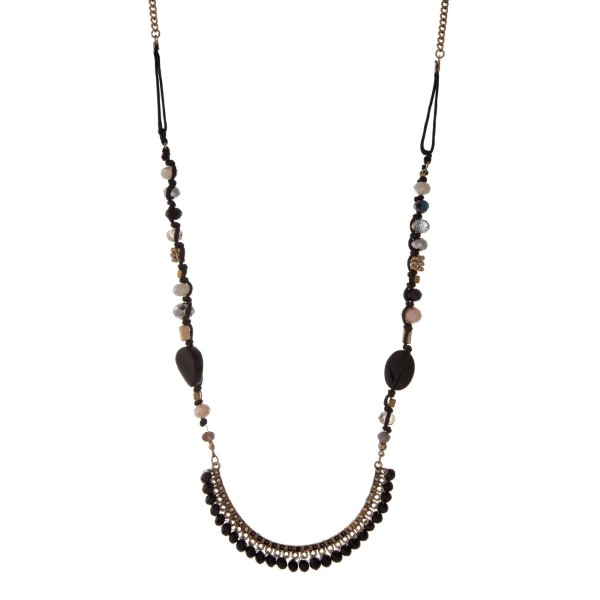 """Gold tone and black cord necklace with a black, gray, and ivory beaded half circle pendant. Approximately 32"""" in length."""