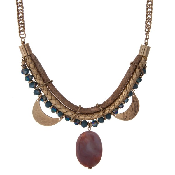 "Gold tone statement necklace with a snake skin pattern, hammered gold tone half circles, blue faceted beads and a purple stone pendant. Approximately 16"" in length."