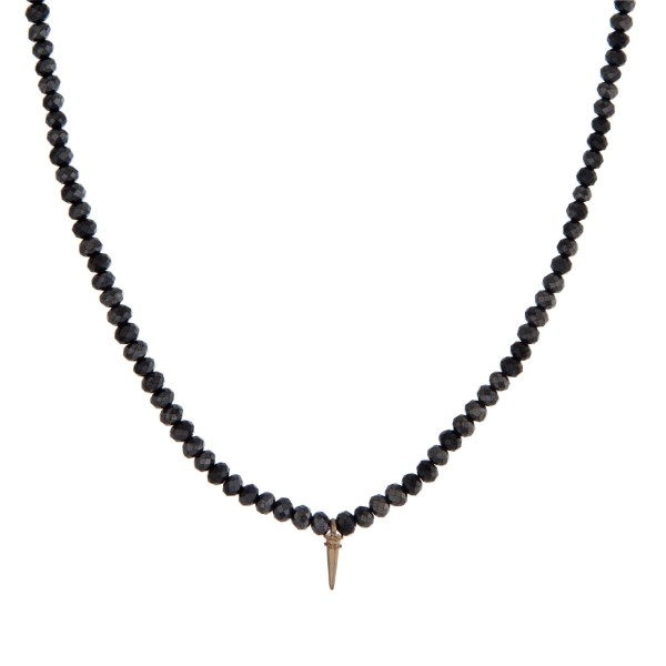 """Gold tone necklace with black faceted beads and a small horn pendant. Approximately 18"""" in length."""