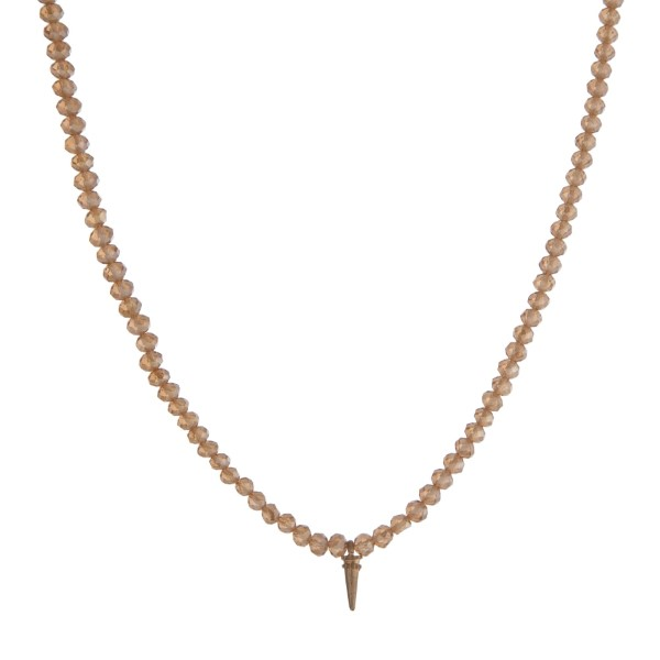 """Gold tone necklace with champagne faceted beads and a small horn pendant. Approximately 18"""" in length."""