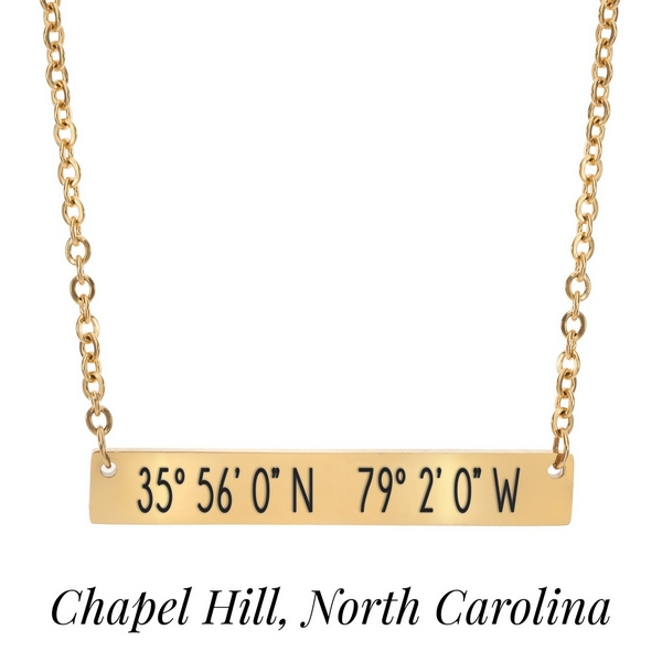 "Gold tone necklace with a bar pendant stamped with the coordinates of Chapel Hill, North Carolina. Approximately 18"" in length."