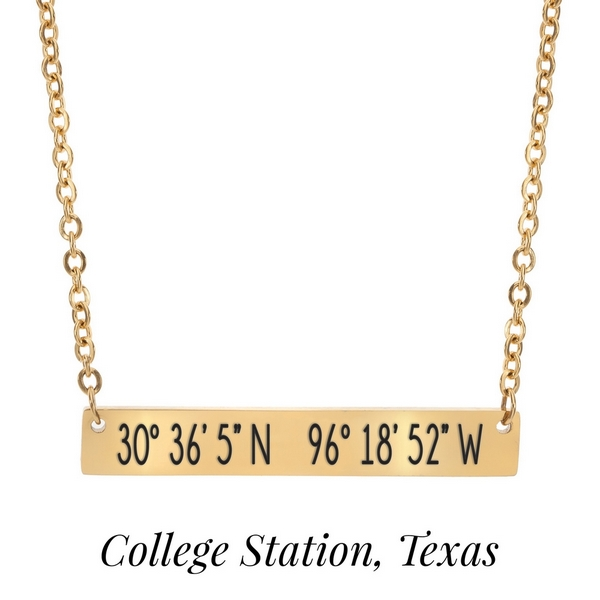 "Gold tone necklace with a bar pendant stamped with the coordinates of College Station, Texas. Approximately 18"" in length."