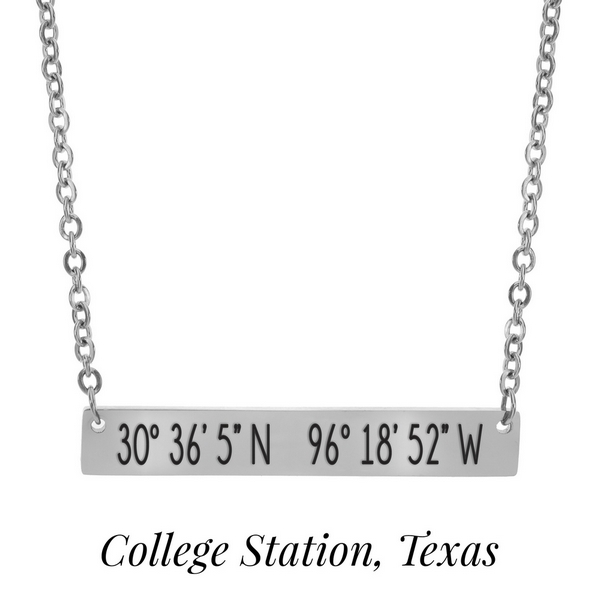 "Silver tone necklace with a bar pendant stamped with the coordinates of College Station, Texas. Approximately 18"" in length."