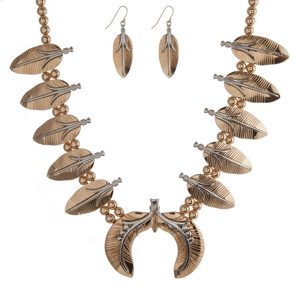 "Gold tone statement necklace set with two tone feathers and a squash blossom. Approximately 21"" in length."