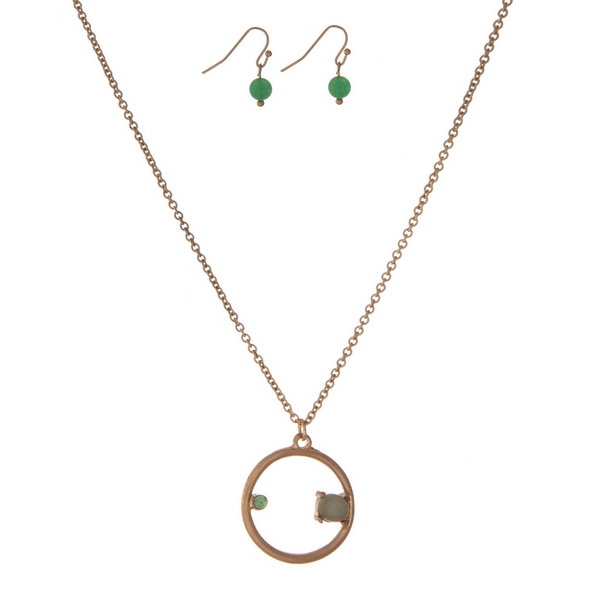 """Dainty gold tone necklace set with a circle pendant, accented with a rhinestone and a green stone. Approximately 16"""" in length."""