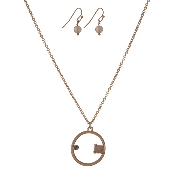 """Dainty gold tone necklace set with a circle pendant, accented with a rhinestone and a gray stone. Approximately 16"""" in length."""