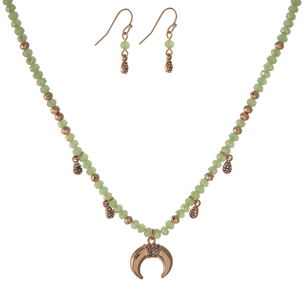"""Dainty gold tone necklace set with light green faceted beads and a crescent pendant and matching fishhook earrings. Approximately 16"""" in length."""