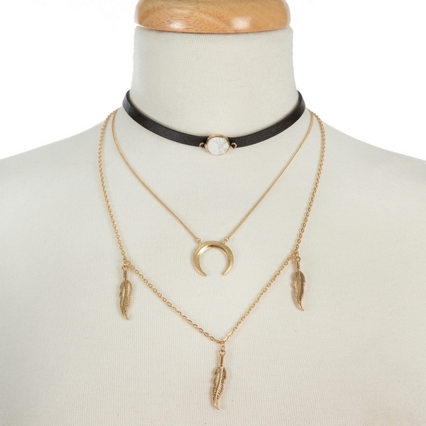 """Black faux leather, layered choker with a white stone, a gold tone layer with a crescent pendant and a layer with feather pendants. Approximately 12"""" to 16"""" in length."""
