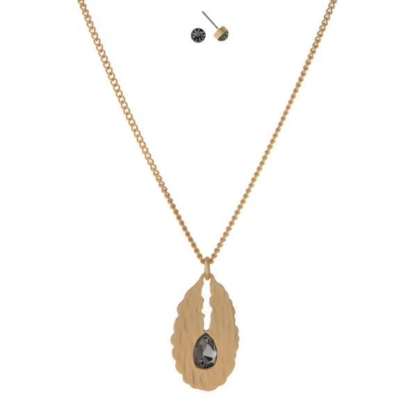 """Gold tone necklace with an oval pendant, accented with a gray rhinestone and matching stud earrings. Approximately 16"""" in length."""