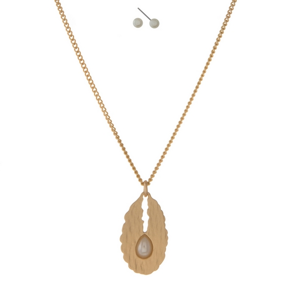 "Gold tone necklace with an oval pendant, accented with a cream pearl and matching stud earrings. Approximately 16"" in length."