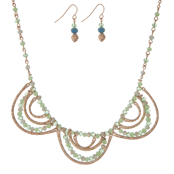 """Gold tone necklace set with light green beads, a scalloped design, and matching fishhook earrings. Approximately 16"""" in length."""