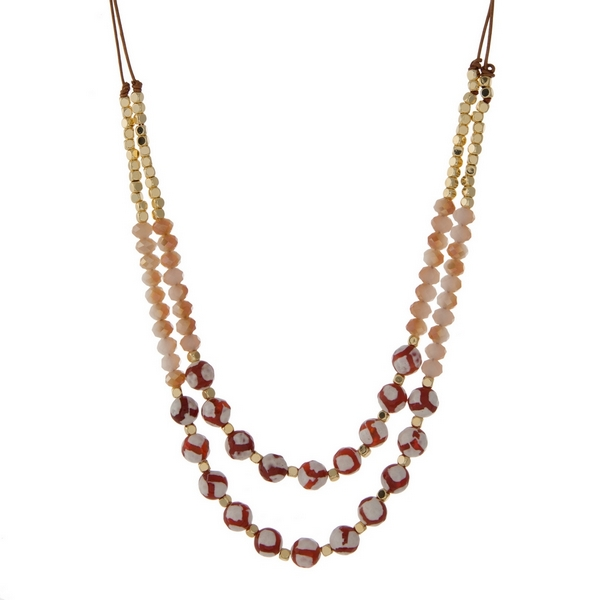 """Brown cord necklace with gold tone, champagne, and red natural stone beads. Adjustable from 14"""" to 27"""" in length. Handmade in the USA."""