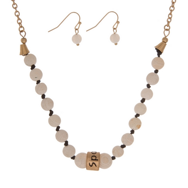 """Matte white, natural stone beaded necklace with a gold tone bead stamped with """"Sparkle"""" and matching fishhook earrings."""