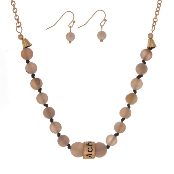 """Matte gray, natural stone beaded necklace with a gold tone bead stamped with """"Achieve"""" and matching fishhook earrings."""