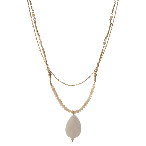 "Gold tone necklace with champagne faceted beads, featuring an ivory teardrop stone pendant. Approximately 32"" in length."