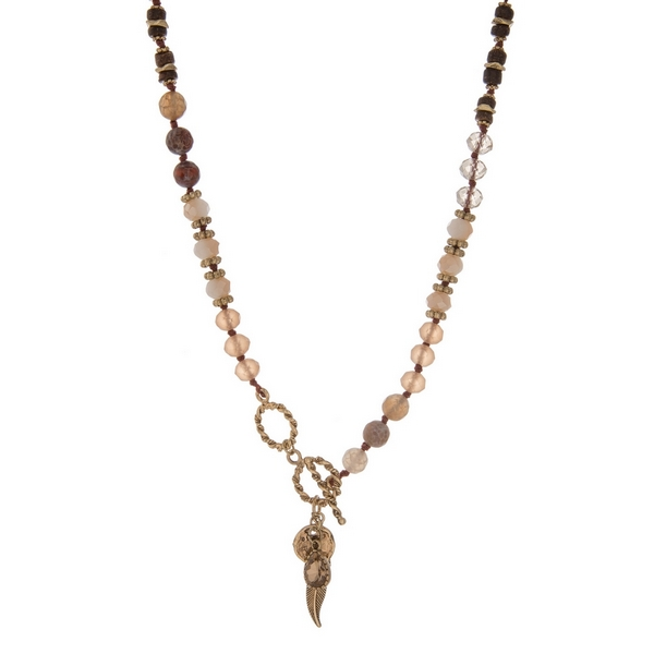 """Ivory, tan, and champagne beaded necklace with gold tone accents and a toggle closure. Approximately 18"""" in length."""