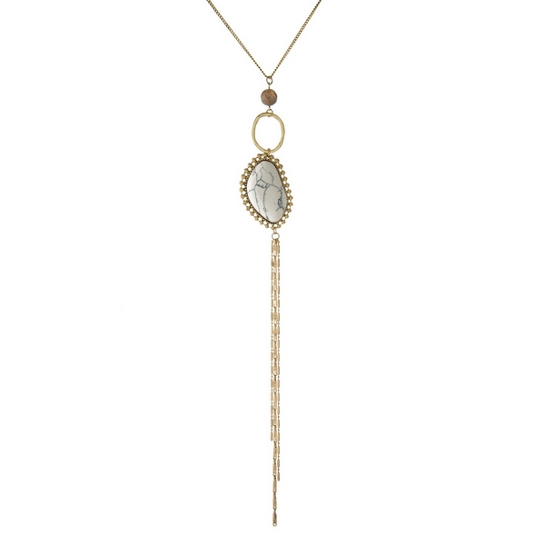 "Gold tone necklace with a white stone pendant, a gray bead and a chain tassel. Approximately 24"" in length."