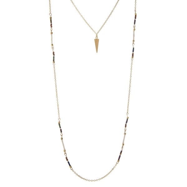 """Dainty gold tone layered necklace with white and iridescent beads, displaying a spear pendant. Approximately 16"""" to 30"""" in length."""