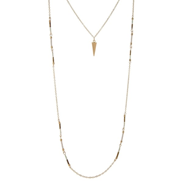 """Dainty gold tone layered necklace with white and mint beads, displaying a spear pendant. Approximately 16"""" to 30"""" in length."""