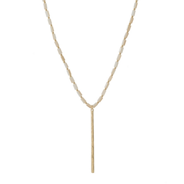 "Gold tone necklace featuring ivory rectangle beads and a hammered bar pendant. Approximately 32"" in length."
