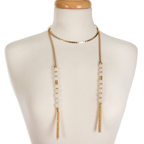 "Gold tone open metal choker featuring tan faux suede pieces with white natural stone beads and chain tassels. Approximately 16"" in length."